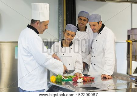 Smiling head chef teaching how to slice vegetables to his students in kitchen