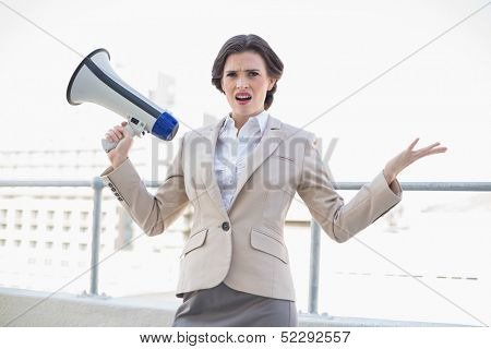 Irritated stylish brown haired businesswoman holding a megaphone outdoors