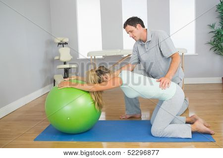 Physiotherapist controlling patient doing exercise with exercise ball in bright room