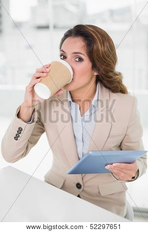 Smiling businesswoman using digital tablet at her desk drinking from disposable cup in bright office