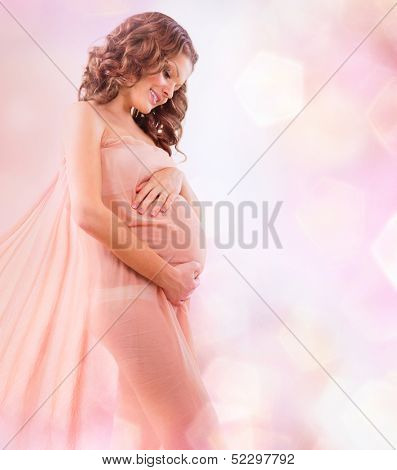 Beauty Pregnant Woman in Blowing Pink Chiffon Shawl. Pregnant Belly. Beautiful Pregnant Woman Expecting Baby. Maternity concept. Baby Shower