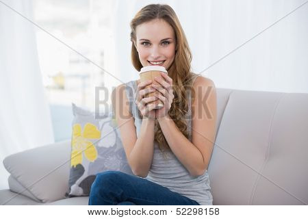 Smiling young woman sitting on couch holding disposable cup at home in the living room