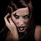 Scary portrait of young woman with aggressive makeup isolated on black background, terrifying witch,