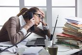 stock photo of secretary  - A stressed business woman looks tired she answer telephones in her office - JPG
