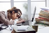 stock photo of boredom  - Tired businesswoman sleeping on the desk in front of the computer screen - JPG