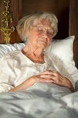 foto of nightgown  - Elderly lady sitting propped up against the pillows in her nightgown and glasses dozing in her bed - JPG