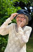 foto of vivacious  - Vivacious elderly lady wearing a hat and elegant lace top laughing outdoors in a summer garden - JPG