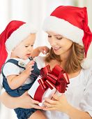 image of santa baby  - happy family mother and baby with gift in red Christmas hats - JPG