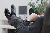 stock photo of disrespect  - A lazy businessman sitting disrespectfully with his legs on the desk - JPG