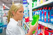 picture of cleaning agents  - a young woman buys cleaning products for cleaning in a supermarket - JPG