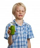 stock photo of disgusting  - A funny boy holding a green smoothie looking disgusted - JPG