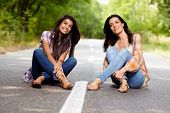 Mother And Daughter Sitting Cross Legged On The Road