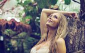 stock photo of blonde  - Blonde beauty in tropical forest - JPG