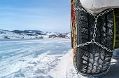 stock photo of icy road  - wheel of a car with chains on snow - JPG