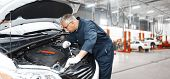 stock photo of auto garage  - Car mechanic in uniform - JPG