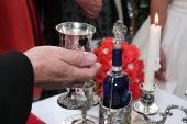 picture of rabbi  - Rabbi holds kiddish cup with wine in front of Groom and Bride