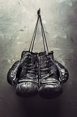 stock photo of boxing ring  - old boxing gloves hang on nail on textur - JPG