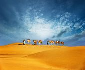stock photo of sahara desert  - Camels travel through sand of desert dunes - JPG