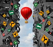 picture of metaphor  - Innovative leadership with a businessman in a hot air balloon flying upward and escaping the confusion of tangled roads and confusing traffic signs as a concept and metaphor for ignoring obstacles and overcoming adversity - JPG