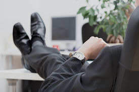 pic of disrespect  - A lazy businessman sitting disrespectfully with his legs on the desk - JPG