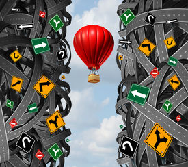 picture of ignore  - Innovative leadership with a businessman in a hot air balloon flying upward and escaping the confusion of tangled roads and confusing traffic signs as a concept and metaphor for ignoring obstacles and overcoming adversity - JPG