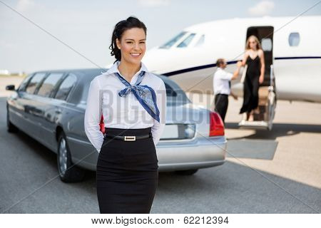 Portrait of attractive airhostess standing against limousine and private jet at airport terminal