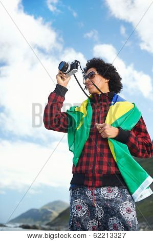 Brasil Brazil soccer fan tourist with camera and flag smiling happy at the beach