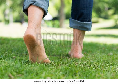 Low section of woman walking on grass in a park