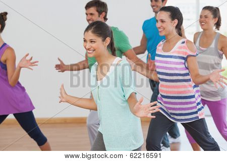 Cheerful fitness class and instructor doing pilates exercise in room