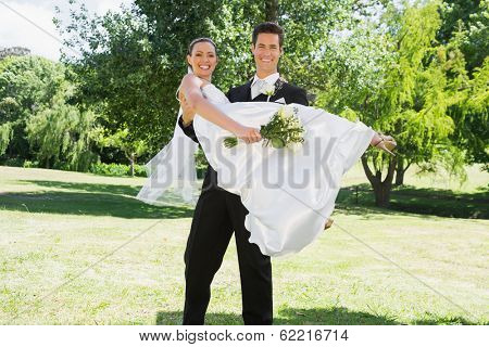 Portrait of happy young groom lifting bride in arms at garden