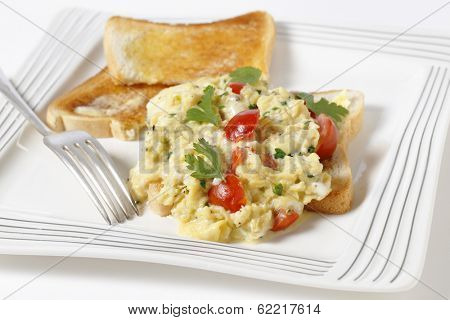 Scrambled egg on toast with cherry tomatoes, parsley and pepper. Cooking in a bain marie allows the tomatoes to be incorporated rather than curdling.