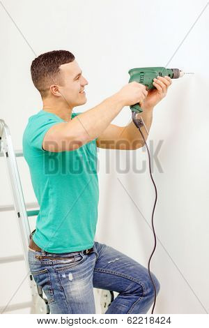 repair, building and home concept - smiling man with electric drill making hole in wall
