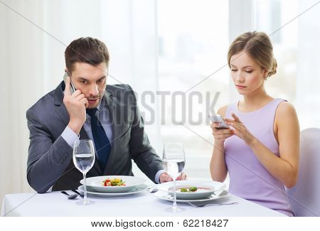 restaurant, couple, technology and holiday concept - busy couple with smartphones at restaurant