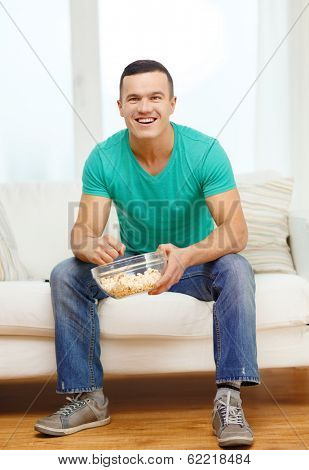 sports, food, happiness and people concept - smiling man watching sports on tv and supporting team at home