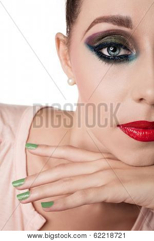 Closeup face of a woman with beautiful red lips and green nails - studio shot of bright fashion makeup