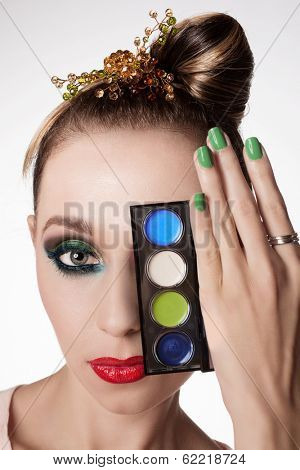 Beautiful woman with sexy red lips and dark glamour eye makeup. Closeup portrait of a female model holding makeup palette in a hand with green manicure