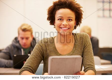 High School Student At Desk In Class Using Digital Tablet