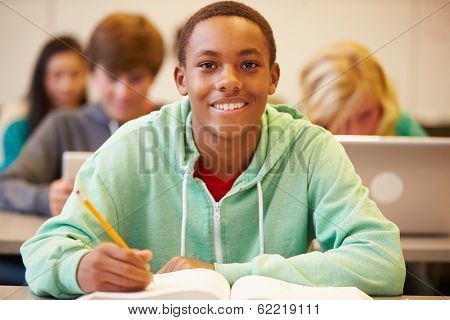 Male High School Student Studying At Desk In Classroom
