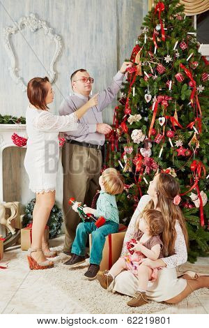 Mother and father decorate Christmas tree, children sit near and look at them