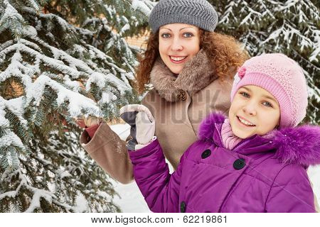 Mother and daughter stand under snow-covered firtree on winter day