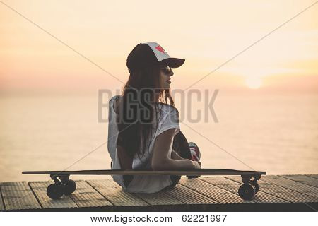 Beautiful fashion skater girl posing with  a skate board
