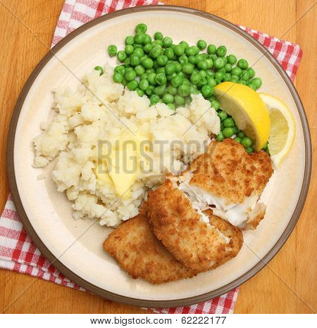 Breaded haddock fish fillets with mashed potato and peas.