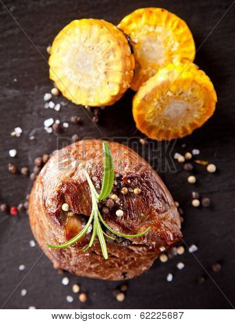 Beef steak served with grilled vegetable and herbs on black stone table