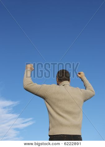 Man with fists in the air signifying success