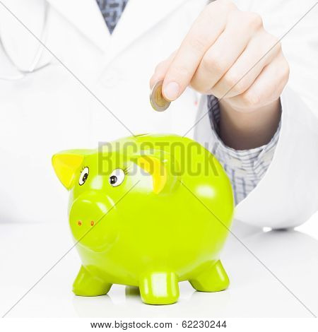 Medical doctor putting a coin into piggy bank