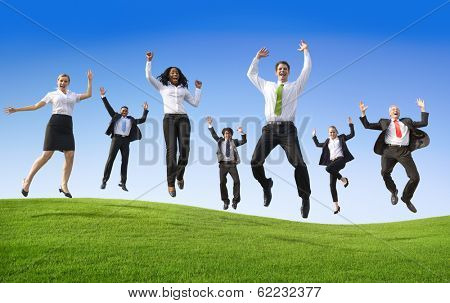 Business People Jumping On a Green Hill