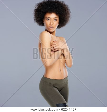 Topless provocative attractive young African American woman with a bushy afro hairstyle posing sideways concealing her breasts with her hands, square format on grey
