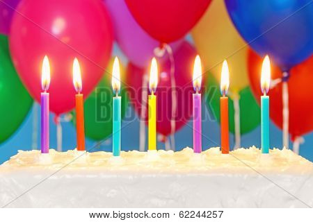 Candles burning on an white iced birthday cake with multicoloured balloons in the background, copy space on the cake to add your own message.