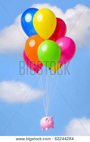 Piggy bank flying in the sky on helium balloons, good image for finance related themes such as Inflation, Savings or Economy.