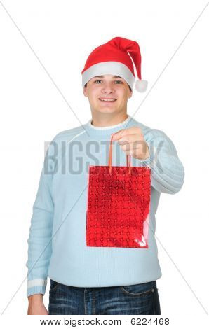 Young man in santa's hat holding present bag isolated on white